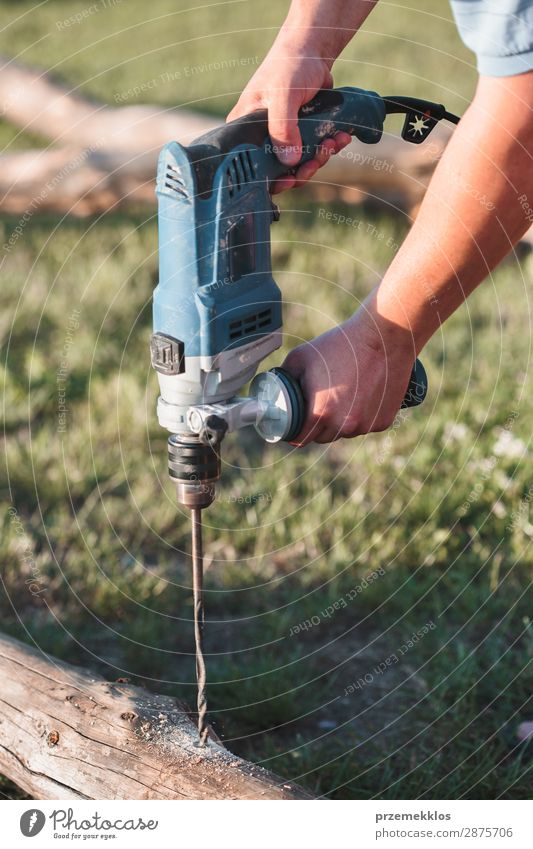 Mann bohrt Loch in Holz bei der Gartenarbeit Haus Arbeit & Erwerbstätigkeit Handwerk Werkzeug Mensch Erwachsene Gras Gebäude nah 35-40 Jahre Kunstgewerbler