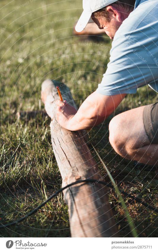Der Mensch setzt Zeichen mit Bleistift im Garten Sommer Arbeit & Erwerbstätigkeit Handwerk Werkzeug Mann Erwachsene Gras Gebäude Hut Holz Stahl weiß Schutz