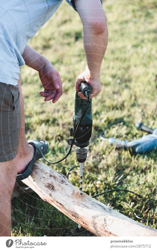 Mann bohrt Loch in Holz bei der Gartenarbeit Sommer Haus Arbeit & Erwerbstätigkeit Handwerk Werkzeug Mensch Erwachsene Gras Gebäude 35-40 Jahre Kunstgewerbler