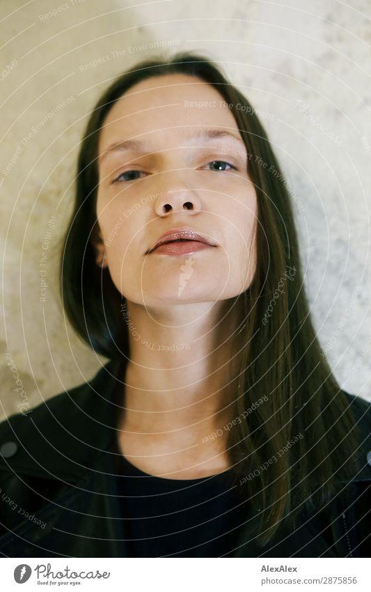 Junge Frau lehnt an der Zimmerwand und schaut herüber deux Lifestyle elegant Stil schön Wohlgefühl Jugendliche 18-30 Jahre Erwachsene T-Shirt brünett langhaarig