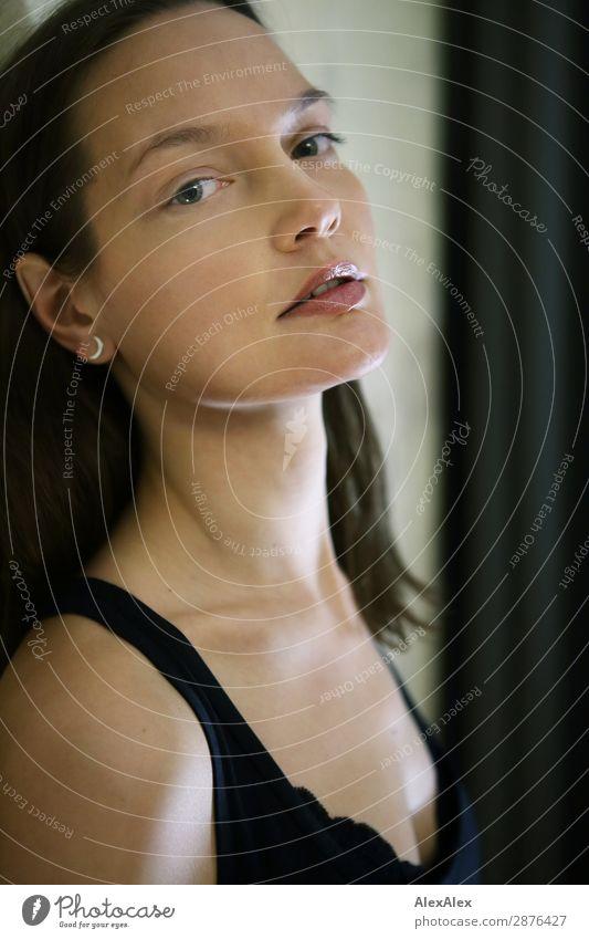 Junge Frau lehnt an der Zimmerwand und schaut herüber Lifestyle elegant Stil schön harmonisch Wohlgefühl Raum Jugendliche Gesicht Dekolleté 18-30 Jahre
