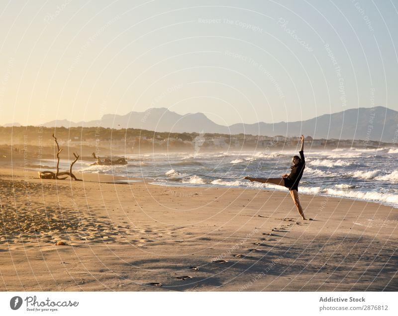 Frau mit Tanz in der Nähe von Wasser am Ufer Tänzer Küste Meer Himmel hochgezogenes Bein winkend Sand blau Jugendliche Balletttänzer Lifestyle Strand