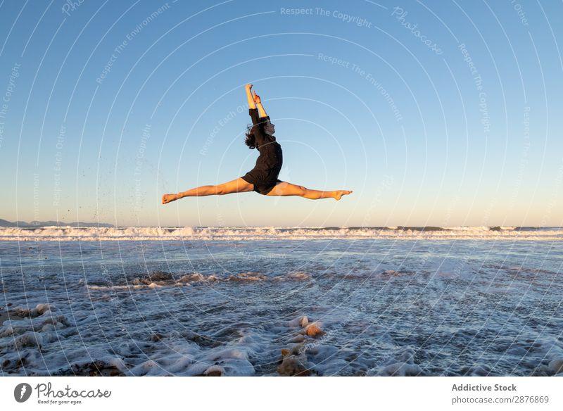 Frau, die am Ufer in der Nähe von Wasser springt. Tänzer Küste springen Meer Beine Seite Luft Himmel winkend Sand blau Jugendliche Balletttänzer Lifestyle