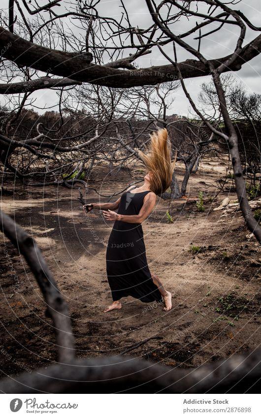 Frau, die auf dem Boden in der Nähe von trockenen Bäumen posiert. Ballerina Körperhaltung Baum geheimnisvoll wiedergeboren dunkel anhaben Landen Holz