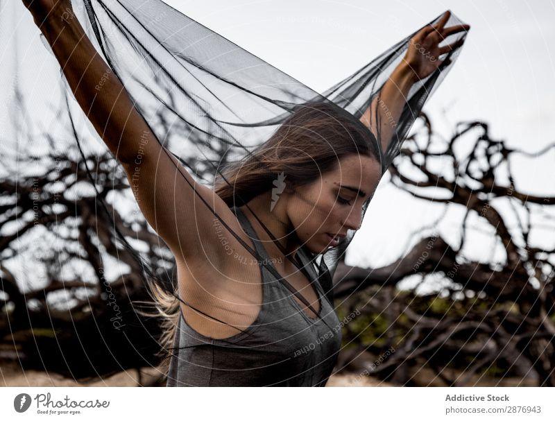 Frau, die auf Zweigen von trockenen Bäumen posiert. Ballerina Körperhaltung Baum geheimnisvoll wiedergeboren dunkel anhaben Holz Ast ausgestreckt Beine