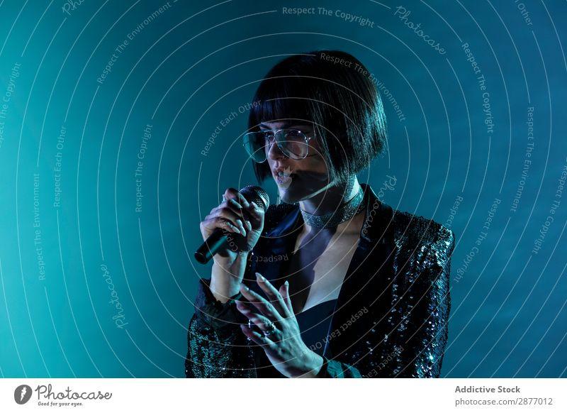 Stilvolle Frau singt auf der Bühne Sänger Leistung Tanzen Gesang brünett Konzert Musik Mikrofon Entertainment Klang Show Lied trendy Mode dunkel Illumination