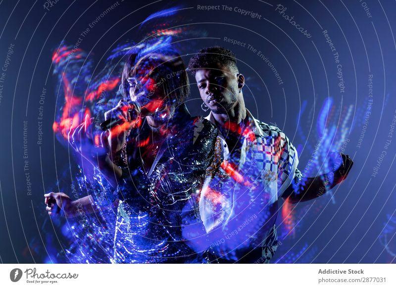 Lichtspuren in der Nähe von Sänger und Tänzer Leistung Fährte mehrfarbig Show Bühne Illumination professionell Energie Musik Konzert Mann Frau Stil trendy Mode