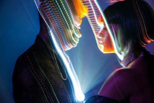 Lichtspuren auf den Gesichtern des Paares Fährte hell mehrfarbig genießen Mann Frau Leistung Show Jugendliche Person gemischter Abstammung multiethnisch