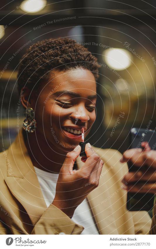 Stylische schwarze Frau, die die Lippen bearbeitet und das Smartphone auf der Straße hält. PDA Vorbehandlung Afroamerikaner elegant Stil Lippenstift