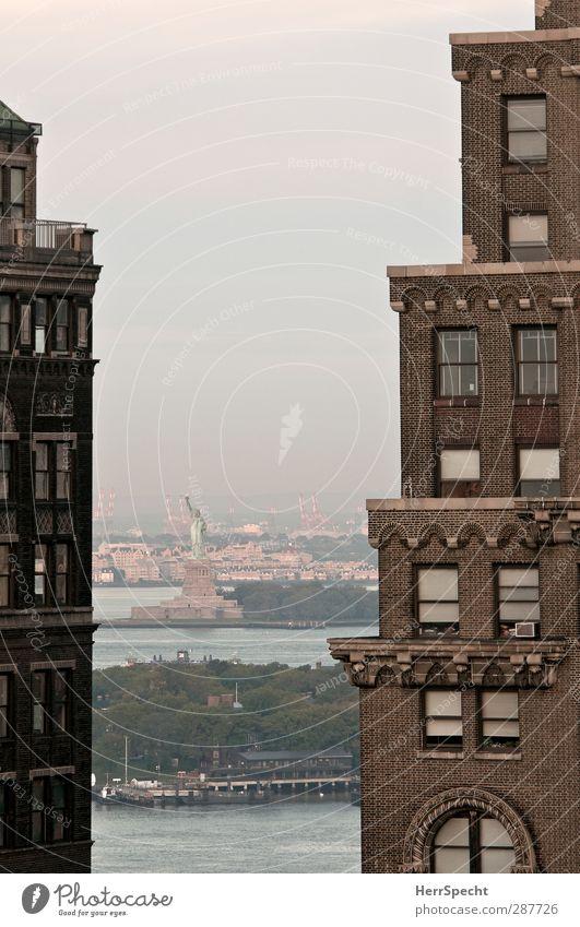 Durchblick New York City Hochhaus Gebäude Fassade Sehenswürdigkeit Wahrzeichen Freiheitsstatue Bekanntheit Stadt braun grau Aussicht Ferne Liberty Island