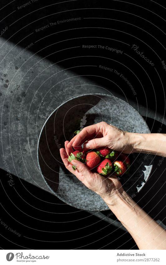 Hände mit Erdbeerhaufen auf dem Teller Hand Erdbeeren Haufen frisch Anhäufung Schalen & Schüsseln Sonnenstrahlen Dunkelheit erleuchten Frucht Lebensmittel süß