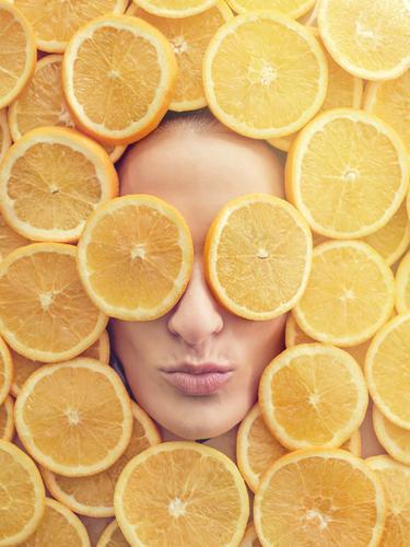 Lächelnde Frau zwischen den Orangenscheiben Gesicht Scheibe frisch Entwurf Glück Jugendliche schön Beautyfotografie Gesundheit attraktiv Frucht Fürsorge Freude