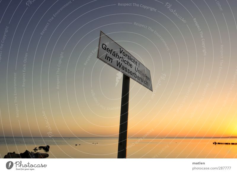 Wo sonst;-)? Landschaft Himmel Wolkenloser Himmel Horizont Schönes Wetter Felsen Küste Meer Metall Schilder & Markierungen Hinweisschild Warnschild blau gold