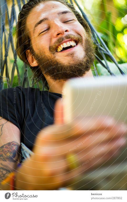am Tablet Mann Mensch Junger Mann Bart Tablet Computer Touchpad berühren Tippen lachen Freude Natur Lächeln Internet Tattoo tätowiert Vollbart Hängematte liegen