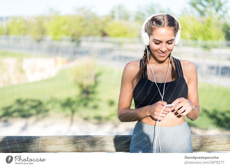 Nahaufnahme eines Porträts einer Frau, die Sport treibt, sich im Freien ausruht, lächelt und Musik hört Joggen Sportlerin laufen rennen Fitness strecken Übung