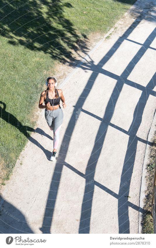 schöne junge Frau, die im Park joggt und im Freien Musik hört. Joggen rennen Fitness strecken üben Mädchen Jugendliche amerikanische Ethnie hören Kopfhörer
