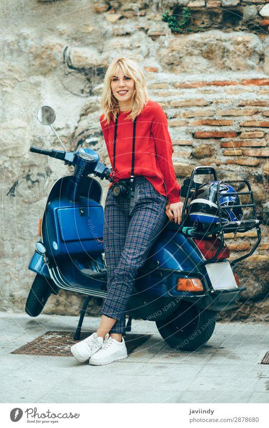 Frau, die auf einem alten blauen Roller sitzt und rote Kleidung trägt. Lifestyle Stil Glück schön Haare & Frisuren Freizeit & Hobby Ferien & Urlaub & Reisen