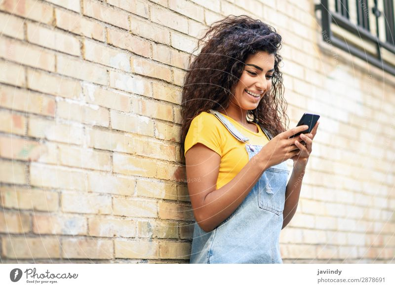 Junge nordafrikanische Frau beim SMSen mit ihrem Smartphone im Freien Lifestyle Stil Glück schön Haare & Frisuren Telefon PDA Technik & Technologie Mensch