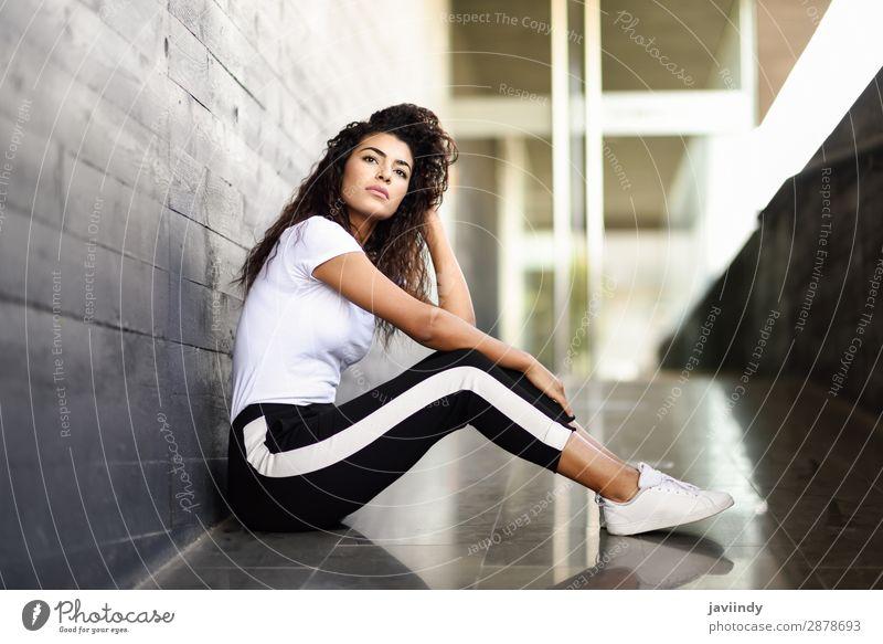 Afrikanische Frau mit schwarzer lockiger Frisur, die auf dem Stadtboden sitzt. Lifestyle Stil schön Haare & Frisuren Gesicht Sport Mensch feminin Junge Frau