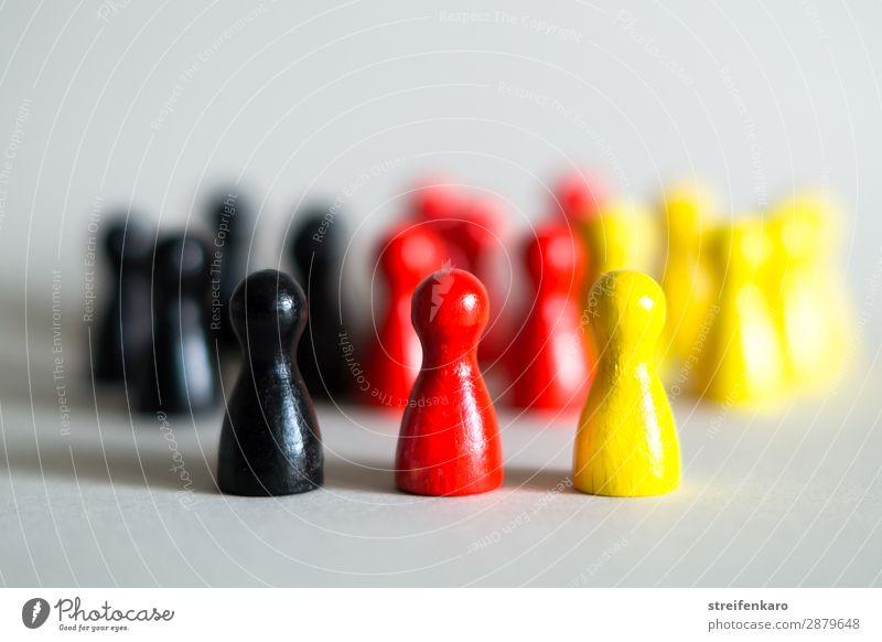 Drei Spielfiguren in Deutschlandfarben stehen vor einer großen Gruppe von Spielfiguren in schwarz, rot, gold Menschengruppe Spielzeug Holz Zeichen frei gelb
