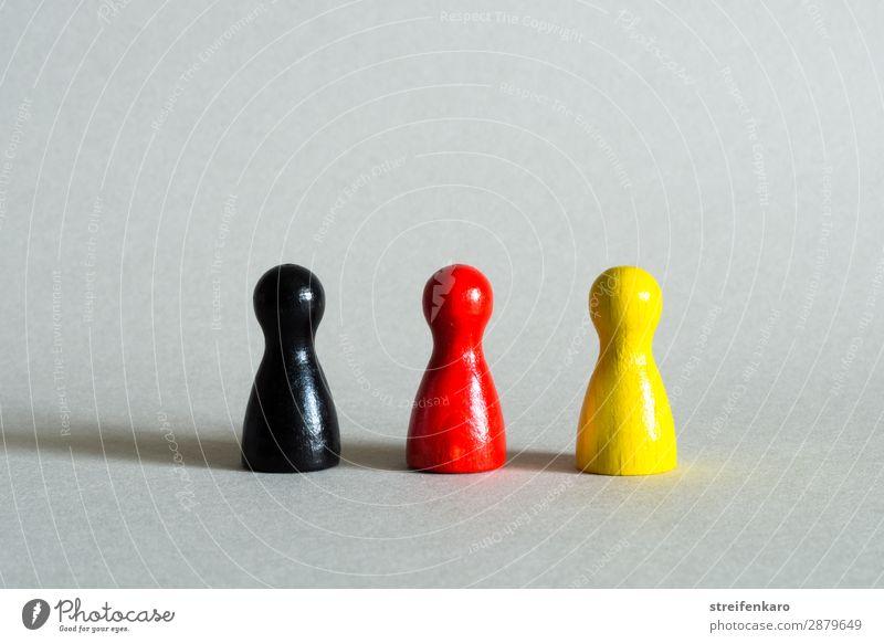 Drei Spielfiguren in schwarz, rot, gelb stehen in einer Reihe Spielzeug Holz Zeichen Fahne gold Einigkeit Gesellschaft (Soziologie) Politik & Staat Regierung