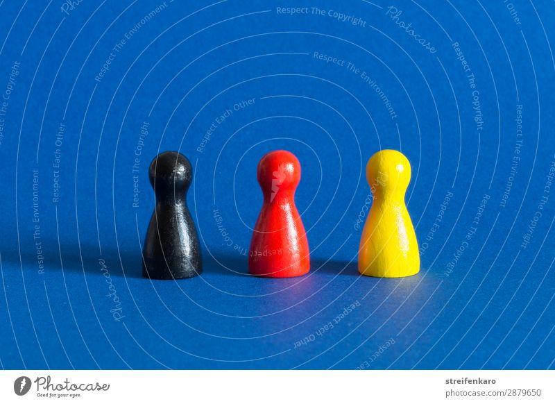Drei Spielfiguren in schwarz, rot, gelb stehen in einer Reihe auf blauem Untergrund Wirtschaft Spielzeug Holz wählen gold Akzeptanz Schutz Zusammensein