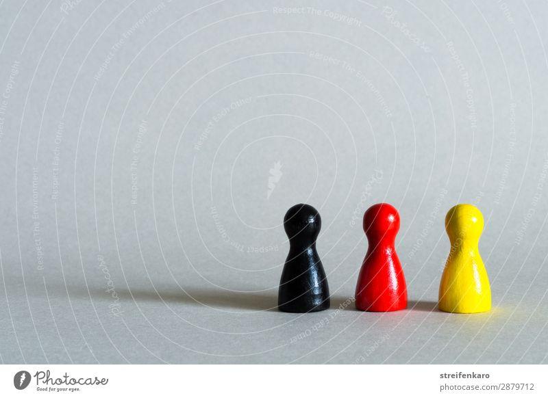Drei Spielfiguren in schwarz, rot, gelb stehen in einer Reihe Menschengruppe Spielzeug Holz Zeichen Zusammensein Gesellschaft (Soziologie) Politik & Staat