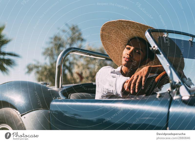 Schwarze Frau fährt ein Oldtimer-Cabriolet. PKW fahren rechtes Lenkrad urwüchsig Glück Straße schwarz vereinigtes königreich Reichtum Wegsehen Strohhut