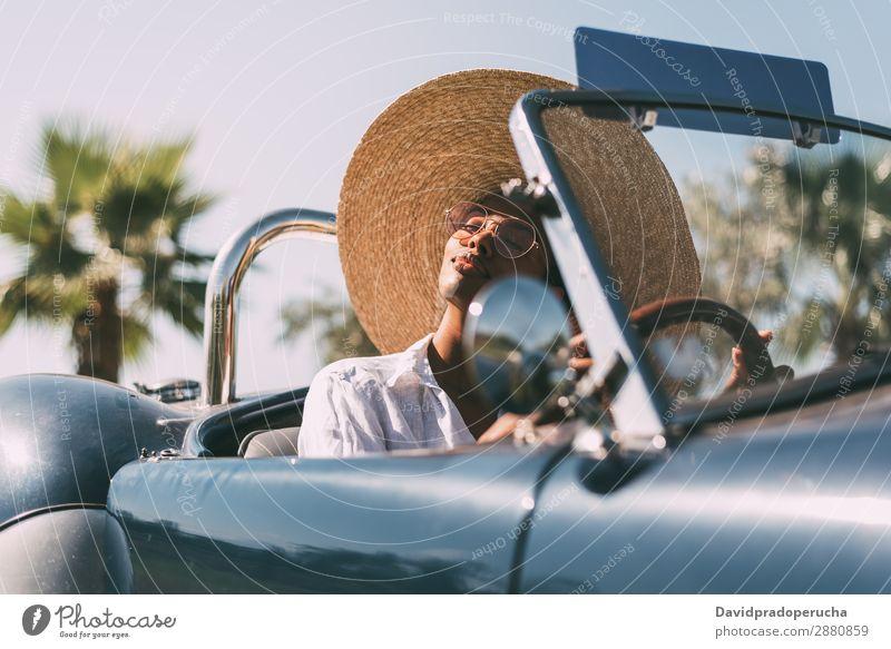 Schwarze Frau fährt ein Oldtimer-Cabriolet. PKW Glück fahren rechtes Lenkrad urwüchsig Straße schwarz vereinigtes königreich Reichtum Strohhut Sonnenbrille