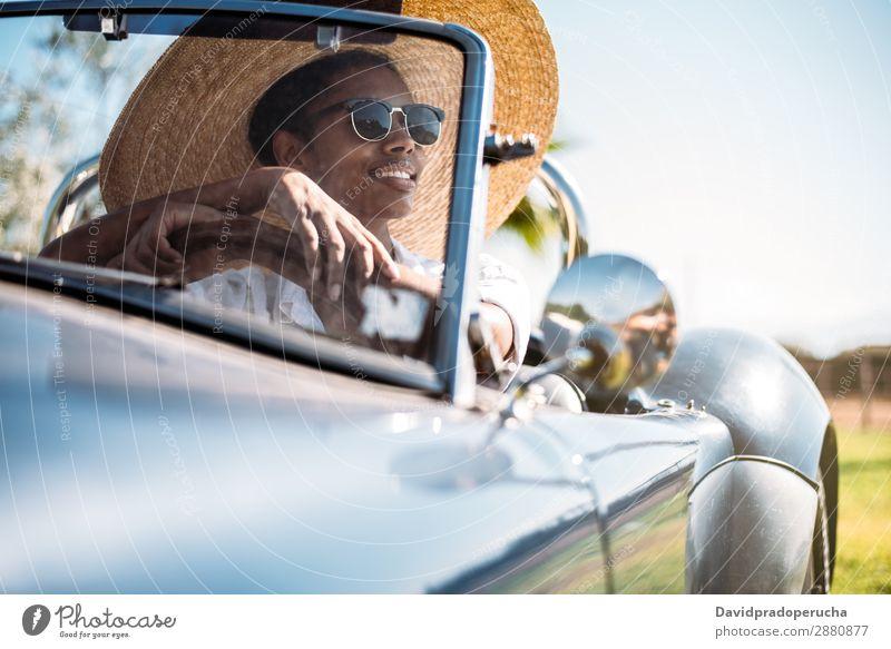 Schwarze Frau fährt ein Oldtimer-Cabriolet. PKW fahren urwüchsig Straße schwarz Reichtum Wegsehen Verkehr Glück klassisch 60's schön altehrwürdig Strohhut