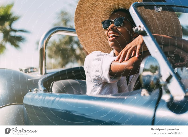 Schwarze Frau fährt ein Oldtimer-Cabriolet. PKW fahren rechtes Lenkrad urwüchsig Glück Straße schwarz vereinigtes königreich Vorderansicht altehrwürdig Reichtum