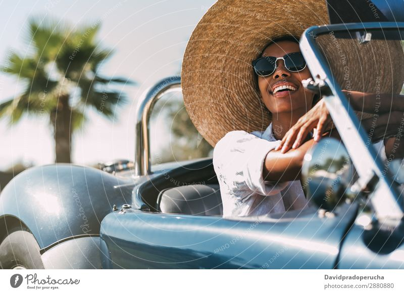 Schwarze Frau fährt ein Oldtimer-Cabriolet. PKW fahren rechtes Lenkrad urwüchsig Straße schwarz vereinigtes königreich altehrwürdig Vorderansicht Reichtum
