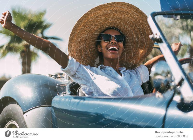 Schwarze Frau fährt ein Oldtimer-Cabriolet. PKW fahren rechtes Lenkrad urwüchsig Straße schwarz vereinigtes königreich Vorderansicht altehrwürdig Reichtum