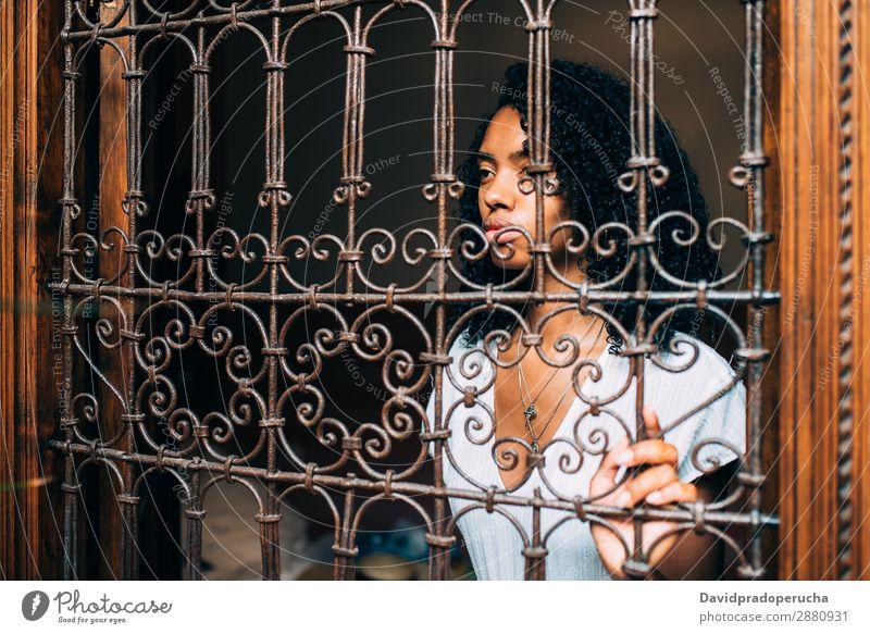 Traurige Frau, gefangen in einem Fenster mit Stahlgittern. Pub Geborgenheit gerieben melancholisch urwüchsig ausgeschlossen Traurigkeit Grillrost getrieben