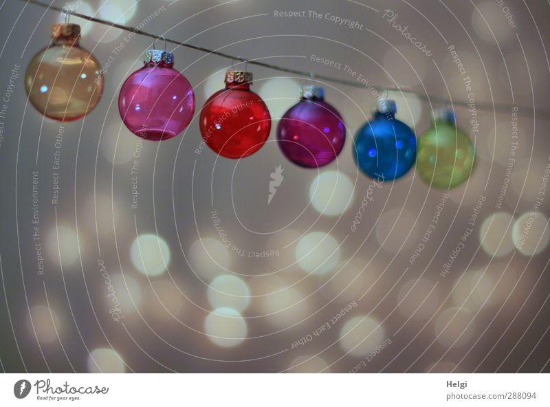 bunte Christbaumkugeln aus Glas hängen an einer Schnur, mit Lichtpunkten im Hintergrund Feste & Feiern Weihnachten & Advent Dekoration & Verzierung Ornament