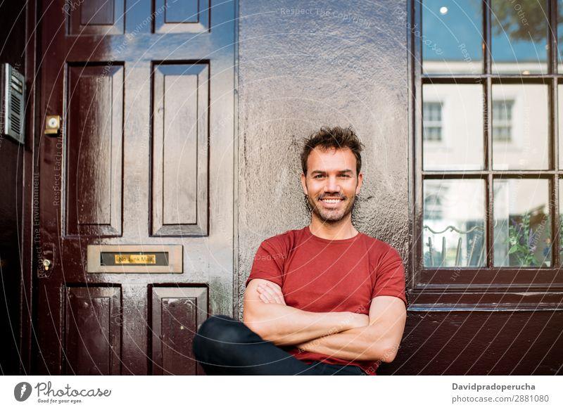 Mann sitzt auf einer Bank auf einem schönen kastanienbraunen Hintergrund. heiter Kaukasier Gebäude Jugendliche Glück Architektur altehrwürdig Lächeln