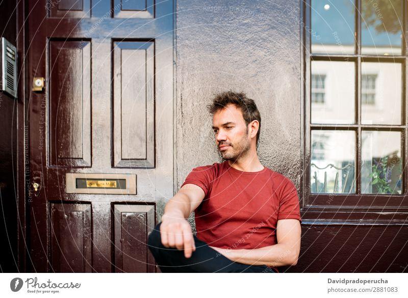 Mann sitzt auf einer Bank auf einem schönen kastanienbraunen Hintergrund. Kaukasier Gebäude Jugendliche Architektur altehrwürdig Nottinghill Dekor Straße sitzen