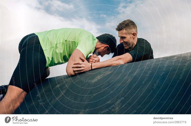 Männer in einem Hindernisparcours beim Aufsteigen auf eine Trommel Lifestyle Freude Sport Klettern Bergsteigen Mensch Mann Erwachsene Hand genießen authentisch