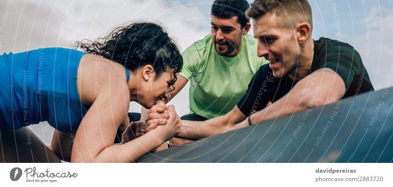Frau klettert auf eine Trommel, unterstützt von ihren Teamkollegen Sport Klettern Bergsteigen Internet Mensch Erwachsene Mann Hand Menschengruppe Fitness