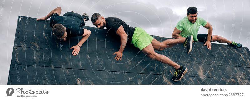 Teilnehmer eines Hindernisparcours beim Klettern an der Umkehrwand Sport Bergsteigen Internet Mensch Mann Erwachsene Menschengruppe stark schwarz anstrengen