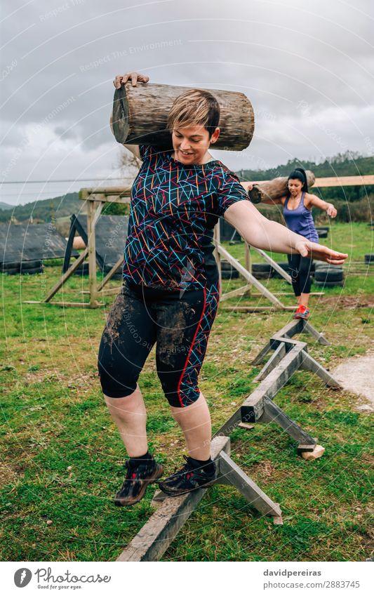Zwei Teilnehmer tragen Gepäckstücke. Zufriedenheit Sport Mensch Frau Erwachsene Mann Lächeln authentisch dreckig stark Kraft anstrengen Konkurrenz