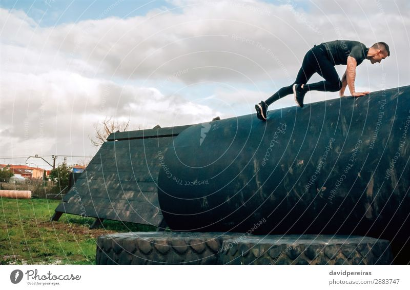 Mann in einem Hindernislauf, der auf eine Trommel steigt. Lifestyle Sport Klettern Bergsteigen Mensch Erwachsene authentisch stark anstrengen jung Ermächtigung