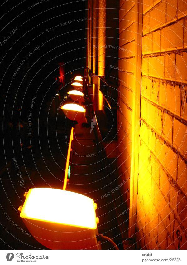 Wand im Licht Lampe Nacht schwarz dunkel Gebäude Fassade Backstein hell gelb Architektur Scheinwerfer Fuge orange