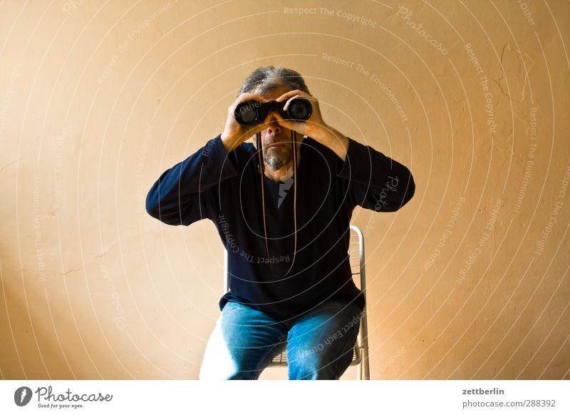 Fernseher Freude Mann Erwachsene Kopf 1 Mensch Blick sitzen Wahrheit Interesse Suche Fernglas Teleskop direkt Blick in die Kamera Farbfoto Innenaufnahme