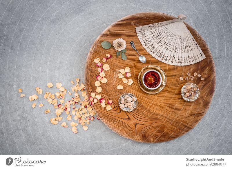 Klassischer Holztisch mit Tee und Rosenblättern Dessert Süßwaren Getränk Teller Löffel Design Tisch Blume Beton Metall natürlich retro braun gelb gold Farbe