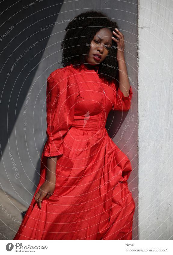 Arabella feminin Frau Erwachsene 1 Mensch Schönes Wetter Mauer Wand Kleid Haare & Frisuren brünett langhaarig Locken beobachten festhalten Blick stehen hell rot