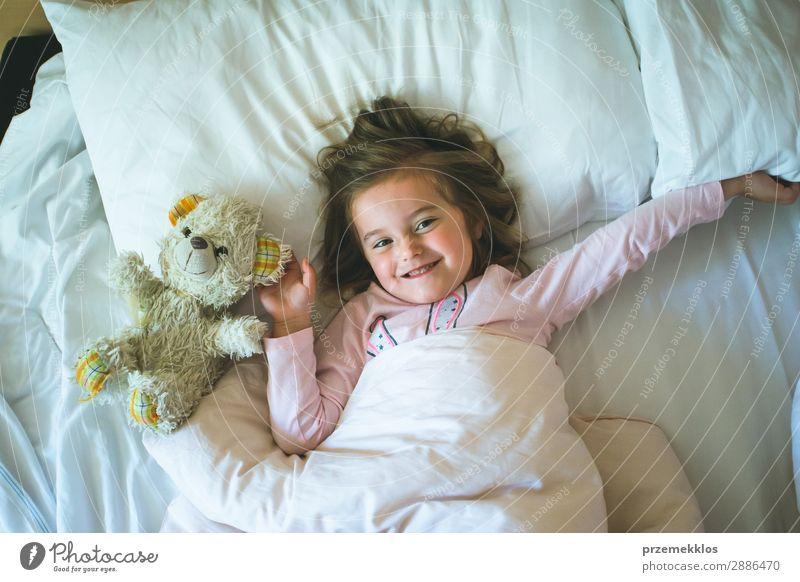 Kleines Mädchen liegt in einem Bett mit Teddybär am Morgen. Glücklicher Morgen. Schlafenszeit. Wochenendmorgen schön Spielen Kind Mensch Frau Erwachsene