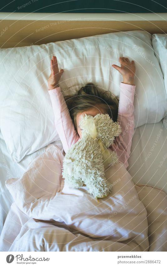 Kleines Mädchen liegt in einem Bett mit Teddybär am Morgen. Glückliche Morgen. Mädchen Kind genießt Morgen im Bett schön Spielen Mensch Frau Erwachsene