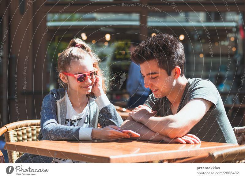 Junge Leute, die im Café sitzen, reden und Mobiltelefone benutzen. Lifestyle Freude Glück Sommer Tisch Restaurant Telefon PDA Technik & Technologie Frau