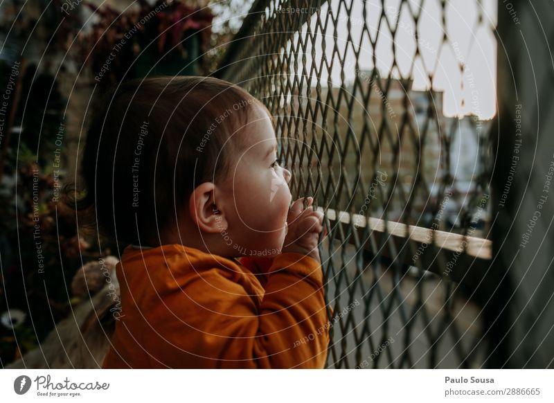 Baby schaut vom Balkon Farbfoto Außenaufnahme Tag Haus Mauer Häusliches Leben Sperrung Quarantäne Quarantänezeit Stadt zu Hause heimwärts Neugier Kind Kindheit
